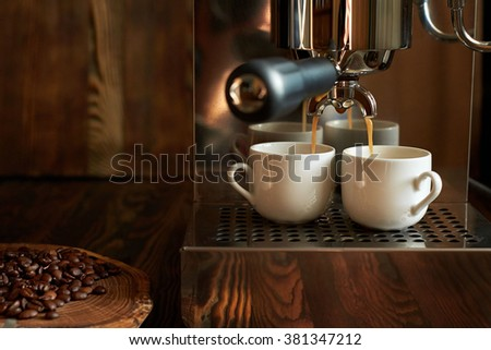 Preparation of espresso in a coffee machine. Coffee being poured into white cup. Metal coffee on a wooden background. Near the coffee beans. Two cups. - stock photo
