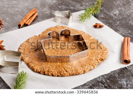 Preparation of gingerbread cookies. Cookie dough, cookie cutters on parchment paper surrounded with christmas tree branch, spices and pine cones, close up, horizontal - stock photo