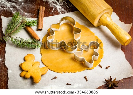 Preparation of gingerbread man cookies. Cookie dough, cookie cutters on parchment paper surrounded with christmas tree branch, spices and rolling pin - stock photo