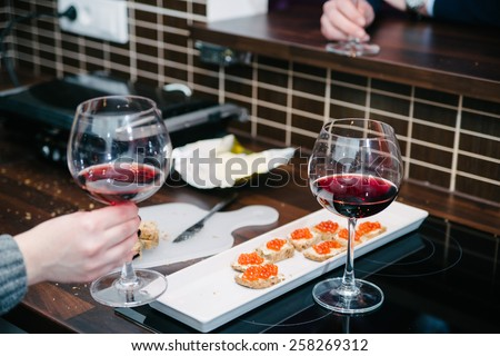 Preparation of red caviar in domestic kitchen, shallow depth of field, focus on the  first piece of bread with caviar on it - stock photo
