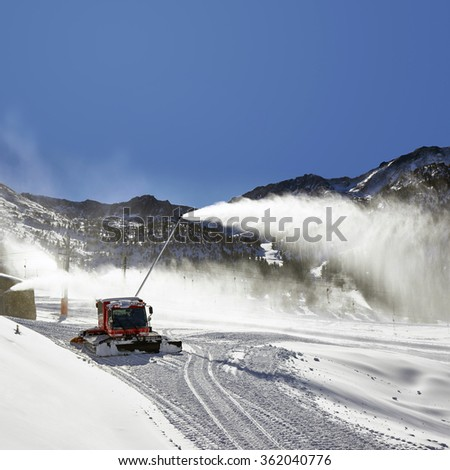 Preparation of ski resort in Pyrenees by red ratrack vehicle and snow canon, Andorra, Europe