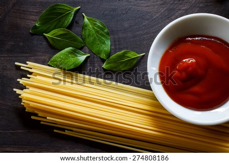 Preparation of spaghetti pasta with tomato ketchup and basil put on black old wooden - stock photo