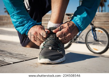 preparation of sportsman tie shoelaces on his running shoe and mountain bicycle at background - stock photo