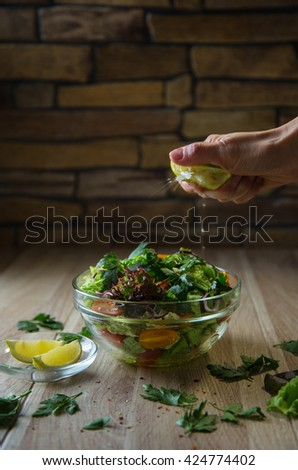Preparation of vegetable salad made with fresh lettuce, chinese cabbage, cherry tomatoes and parsley on a wooden table. Squeezing of lemon juice - stock photo
