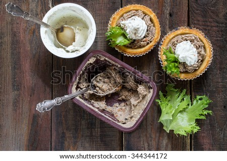 Preparation tartlets with liver paste, ricotta and lettuce on a wooden table - stock photo