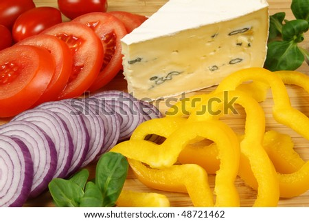 Preparations for a salad - colorful fresh vegetable ingredients. Tomatoes, peppers, arugula,  onions and soft cheese. - stock photo