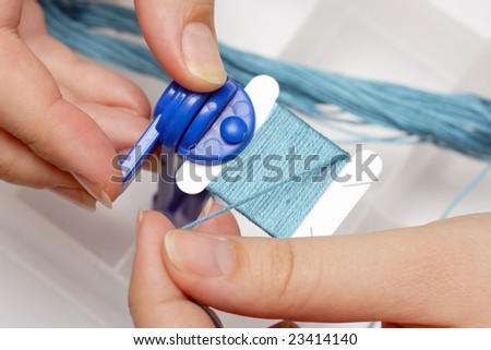 Preparations for embroidery (cross stitch). Thread winding on the coil (bobbin). - stock photo