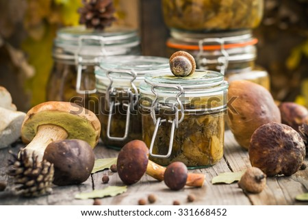 Preparations in the kitchen: mushrooms marinated in jars on a wooden table - stock photo
