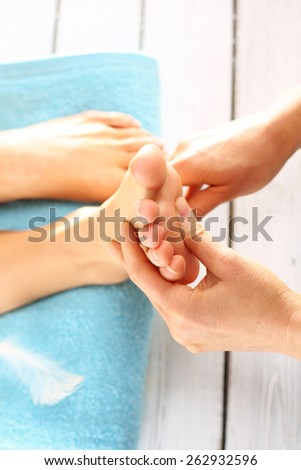 Prepare feet before the summer. Woman in a beauty salon for pedicure and foot massage. - stock photo