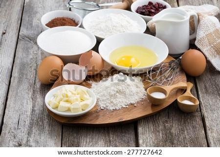 prepared baking ingredients on wooden table, horizontal - stock photo