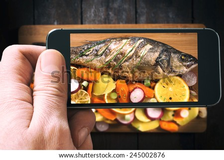 Prepared Bass fish with vegetables and fruit from above on wooden background photographed by phone - stock photo