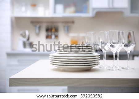 Prepared clean dishes for dinner party on a table in the kitchen - stock photo
