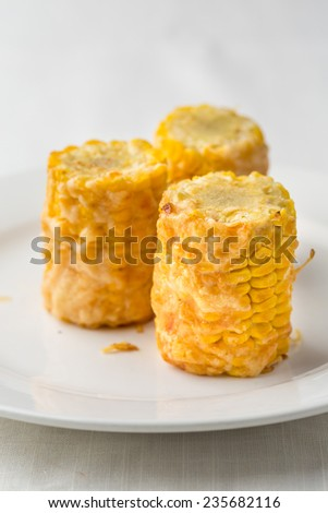 prepared corn pieces with cheese on white plate - stock photo