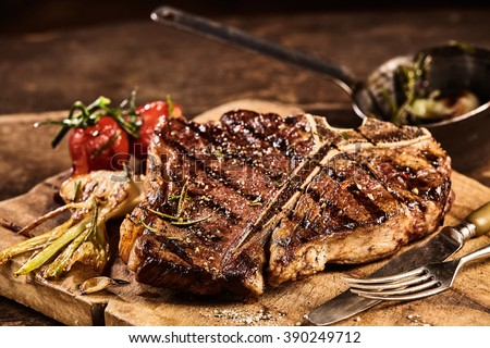 Prepared grilled large t-bone steak surrounded by tomatoes and garnished with seasonings next to fork and knife on cutting board - stock photo