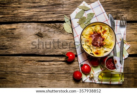 Prepared ravioli with tomato sauce in a Cup. On wooden background. Top view - stock photo