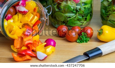 Prepared salad in glass storage jars.Chopped ingredients flowing out of one on it's side. - stock photo