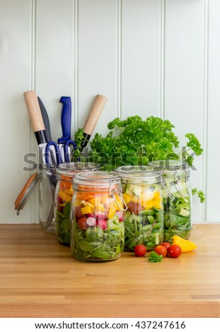 Prepared salad in glass storage jars in kitchen with utensils. Space for text. Vertical..