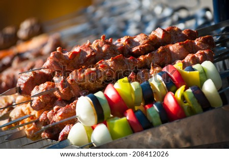Prepared shashlik, lamb meat grilling on metal skewer and grilled vegetables - stock photo