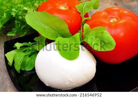 prepared the ingredients for the salad caprese. Tomato, mozzarella, arugula and basil  - stock photo