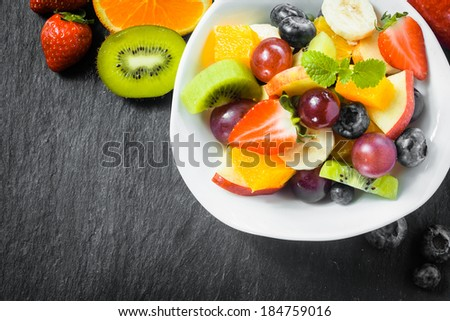 Preparing a bowl of tasty fresh fruit salad for breakfast with tropical ingredients on a rustic slate kitchen counter, overhead view with copyspace - stock photo