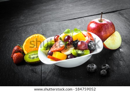 Preparing a delicious colorful bowl of fresh fruit salad with tropical fruit including blueberries, apple, orange, kiwifruit and strawberries on a slate kitchen surface - stock photo