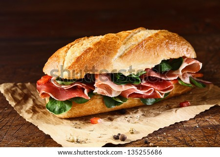 Preparing a delicious ham and fresh basil baguette on a sheet of grungy oily paper with remnants of seasoning - stock photo