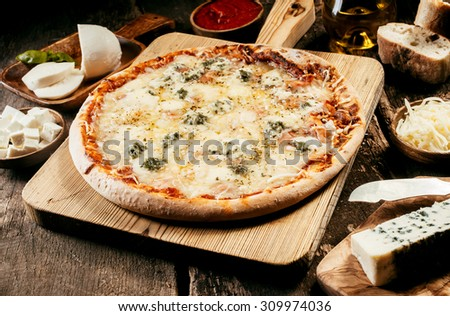 Preparing a four cheeses Italian pizza in a rustic kitchen with individual bowls of mozzarella, gorgonzola, emmental and goat milk cheese around a baked pizza on a wooden board - stock photo
