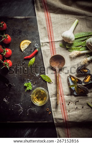Preparing a gourmet savory mussel appetizer with boiled marine mussels, olive oil, chili pepper, tomatoes, garlic, springonions and herbs, view from above scattered on a kitchen counter - stock photo