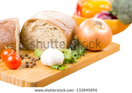 Preparing a savoury vegetarian meal with a fresh garlic, rosemary and parsley, cherry tomatoes, onion and bread on a wooden chopping board with a bowl of mixed vegetables in the background - stock photo
