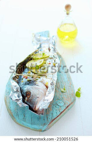 Preparing a whole fresh fish to be baked on a barbecue in a foil wrapper with lemon, olive oil , spices and herbs arranged on a wooden board with the head to the camera - stock photo