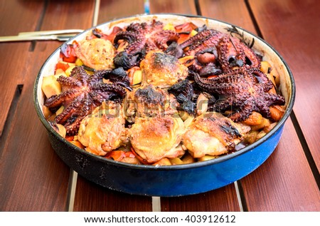 Preparing and Cooking of octopus and chicken in traditional Balkan Croatian Greek Mediterranean meal Peka in metal pots called sac sach or sache or a lid. Dish is ready on a wooden table. - stock photo