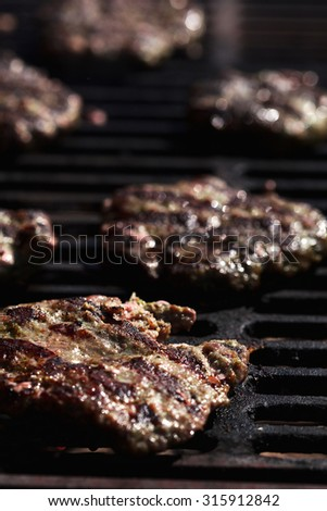 Preparing beef patties for burgers on grill BBQ - stock photo