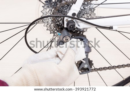 Preparing bicycle for a new season. Hand with cloth cleaning derailleur