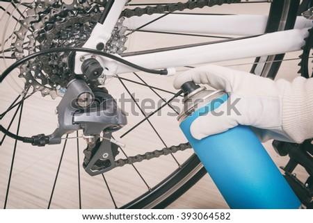 Preparing bicycle for a new season. Lubricating freewheel or cogwheel - stock photo