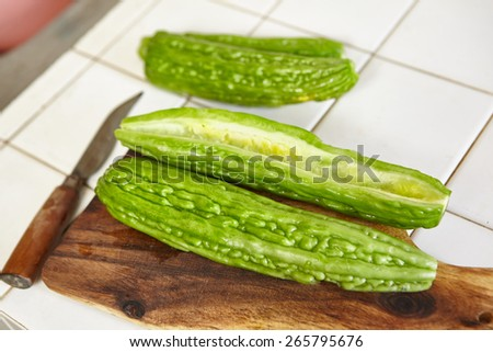 Preparing bitter melon for cooking - stock photo