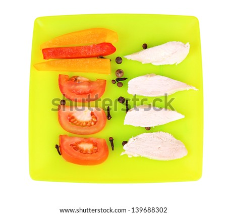 Preparing chicken stir fry with vegetables and spices on color plate, isolated on white - stock photo