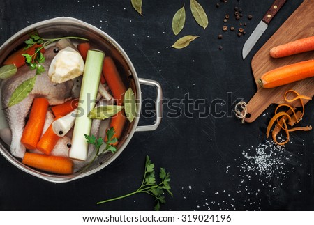 Preparing chicken stock (bouillon) with vegetables in a pot. Black chalkboard as background. Kitchen worktop scenery from above. Layout with free text space. - stock photo