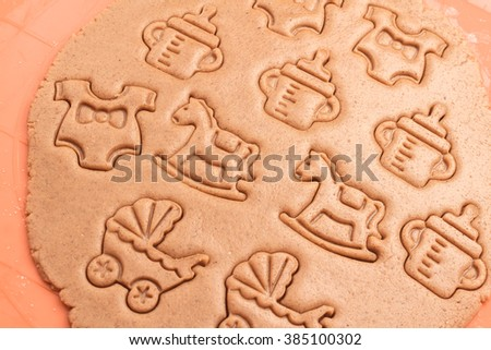 Preparing cookies of baby shower. Sweet dough with various funny ornaments on it