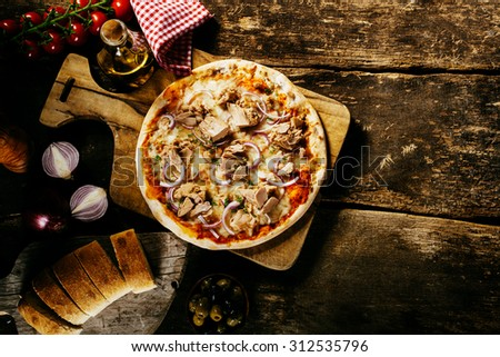 Preparing delicious homemade tuna pizza in a rustic kitchen on an old wooden counter served with fresh bread and condiments, overhead view with copyspace - stock photo