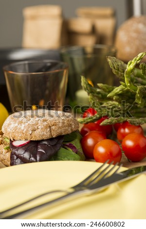 Preparing delicious salad rolls for lunch on healthy wholegrain rolls with tomatoes, baby spinach leaves and asparagus - stock photo