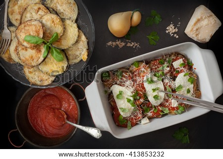 Preparing eggplant parmigiana, fifth step, spoon over more tomato sauce, some mozzarella slices, grated parmesan and basil leaves.  - stock photo