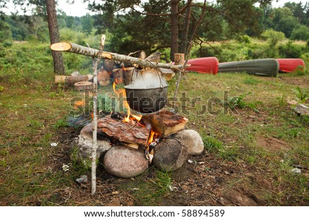 Preparing food on campfire in wild camping - stock photo