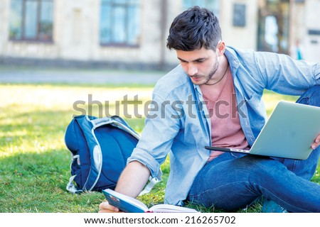 Preparing for tests. Cute male student holding a laptop and reading a textbook while sitting on the grass near the campus of the University at the break. - stock photo