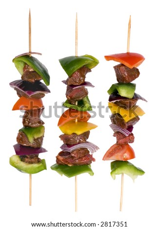 Preparing fresh beef steak shishkabobs with vegetables ready for the grill. Isolated on white - stock photo