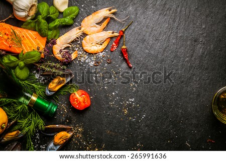 Preparing fresh seafood in the kitchen with gourmet salmon fillets, pink shrimp, and steamed mussels surrounded by fresh herbs and spices, with copyspace