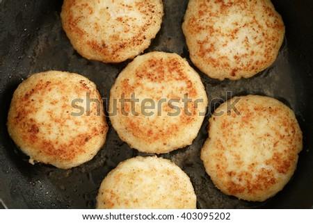 preparing fried fish cakes on pan, shallow focus - stock photo