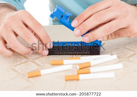 Preparing handmade cigarettes using rollings and tobacco to fill sticky paper and filter and satisfy habits - stock photo