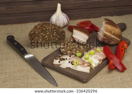 Preparing home-made snacks for the guests. Cutting board with smoked bacon and bread. Raw bacon. Whole grain bread.  - stock photo