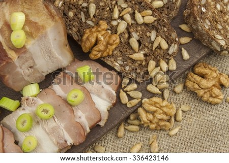 Preparing home-made snacks for the guests. Cutting board with smoked bacon and bread. Raw bacon. Whole grain bread  - stock photo