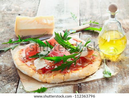 Preparing homemade ham pizza with fresh ingredients including thinly sliced ham, cheese, herbs and tomato - stock photo